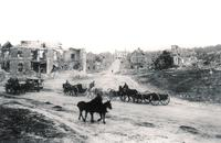 Canadian troops passing through a village devastat